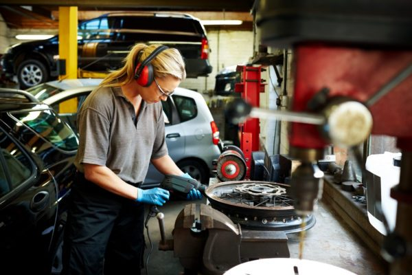 Female mechanic working on car rims in auto garage